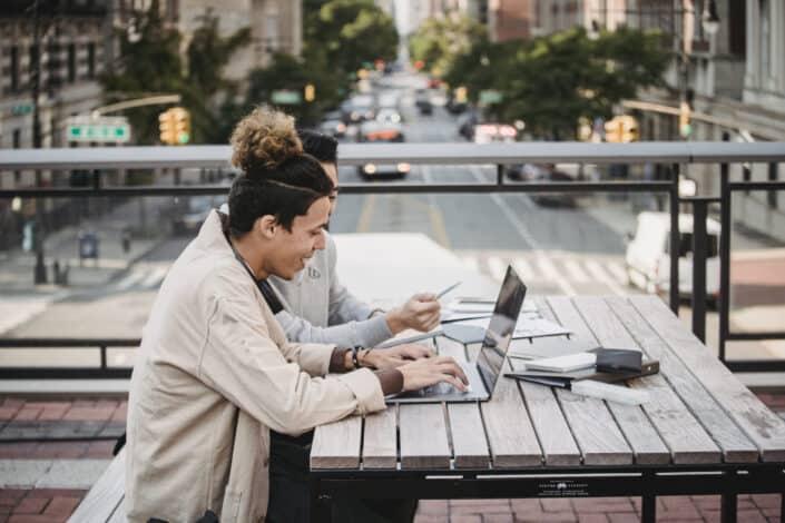 Amigos sentados en la terraza de la azotea discutiendo algo en su computadora portátil