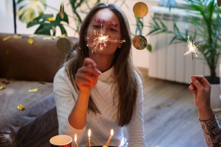 dama con confeti en la ceja jugando con un poco de fuegos artificiales