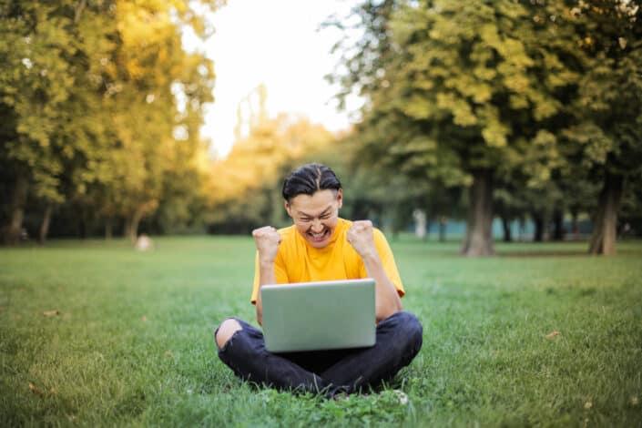 un hombre sentado en el césped con su computadora portátil expresando su éxito