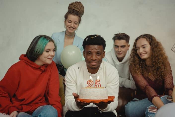 Celebrante de cumpleaños sosteniendo su pastel con sus amigas