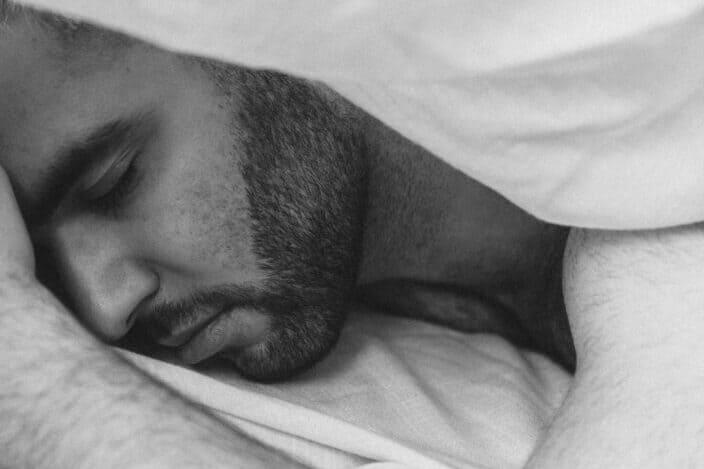 hombre barbudo durmiendo pacíficamente bajo las sábanas