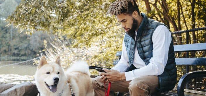 hombre sentado con su perro en un parque