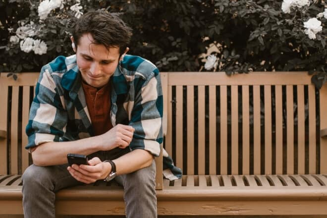 Mensajes positivos cortos - Hombre sentado en un banco de madera sonriendo sobre algo en su teléfono
