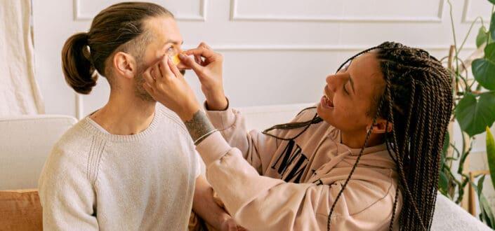 Mujer poniendo una curita en la cara del hombre.