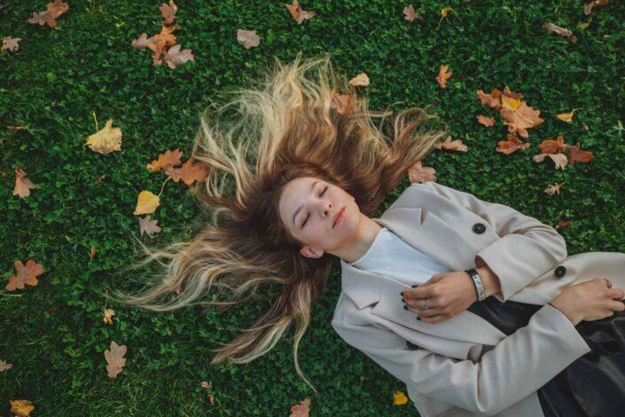 Señora acostada sobre una hierba verde con hojas secas caídas
