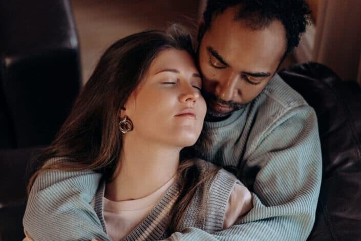 pareja abrazándose en un sofá de cuero