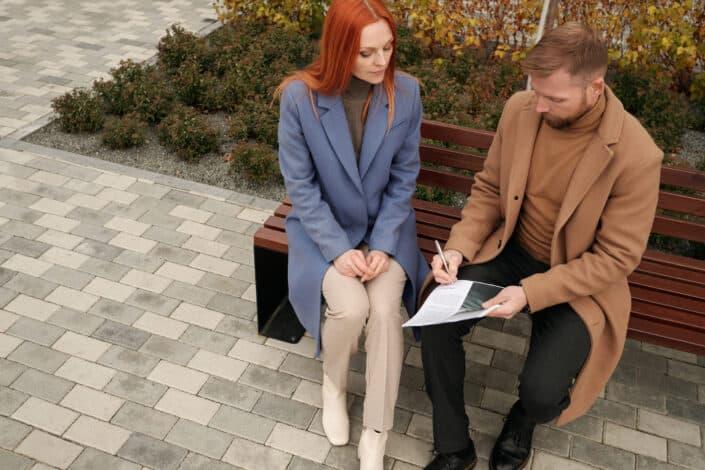 hombre y mujer sentados en un banco discutiendo sobre algo