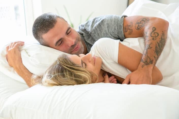 dulce pareja abrazándose en su cama