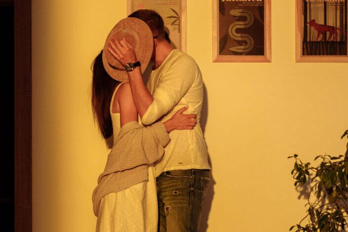 una pareja cubriendo sus rostros con un sombrero mientras se besan