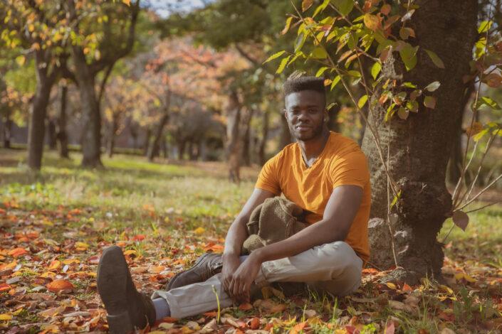hombre con una camisa naranja sentado bajo los árboles