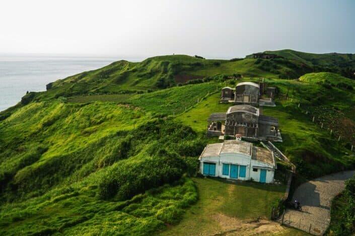 Tres casas en la cima de la montaña verde montañosa