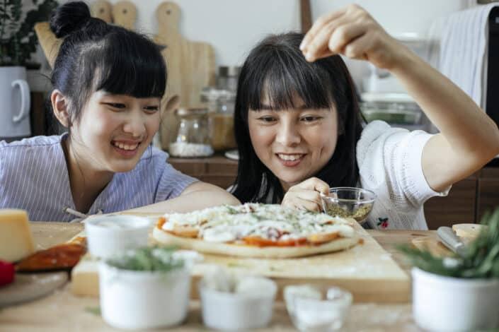 Dos chicas haciendo pizza