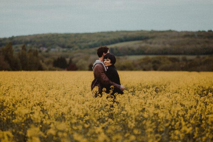 pareja abrazándose en medio de flores doradas