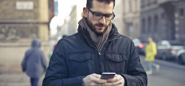 Guy mirando su teléfono mientras camina por una calle