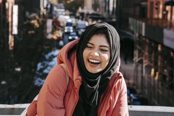 Alegre mujer étnica en hijab riendo