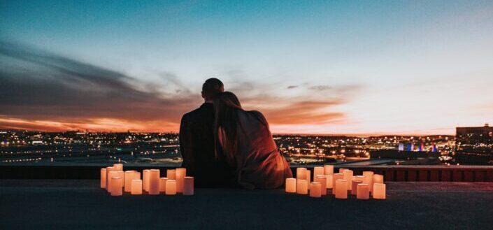 pareja sentada en el campo frente a la ciudad