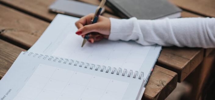 Mujer de cultivo haciendo horario en planificador