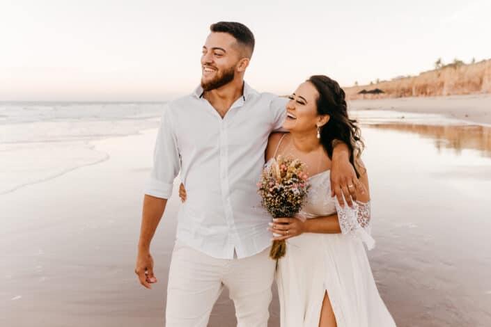 Encantado de pareja de recién casados caminando en la playa