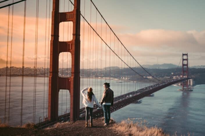 Hombre y mujer de pie cerca del puente Golden Gate