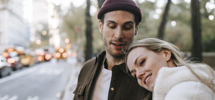 Pareja sonriente teniendo cita romántica en las calles de la ciudad