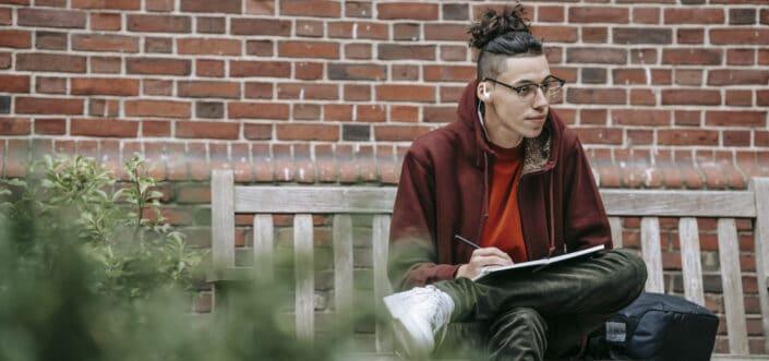 Hombre escribiendo en un cuaderno mientras está sentado en un banco