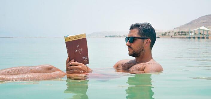 Hombre con gafas de sol leyendo un libro mientras está en el agua