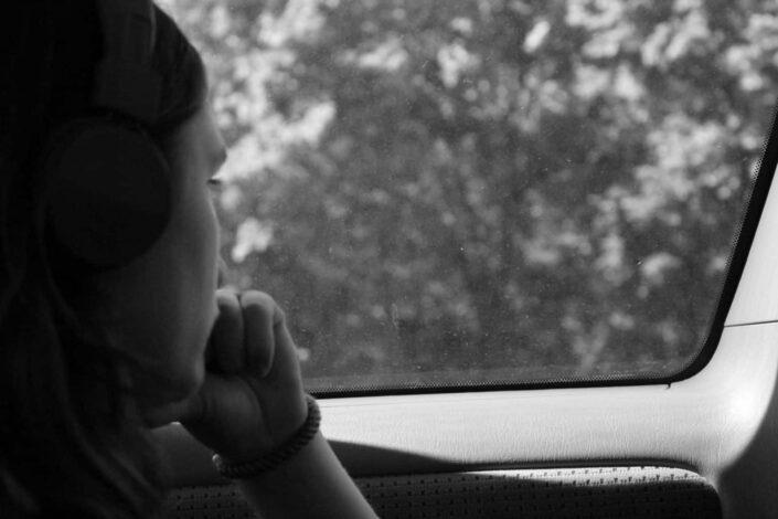 Mujer sola mirando afuera a través de la ventanilla del coche