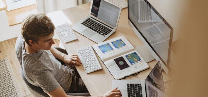 hombre usando 3 computadoras en su trabajo