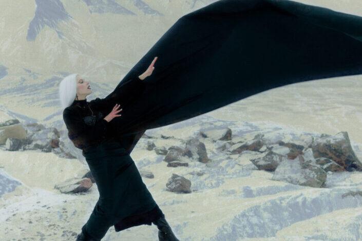 una foto única de una mujer de cabello plateado en una montaña nevada