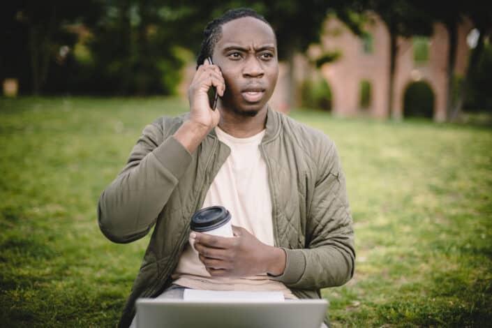 hombre con café en la mano hablando con alguien en su teléfono