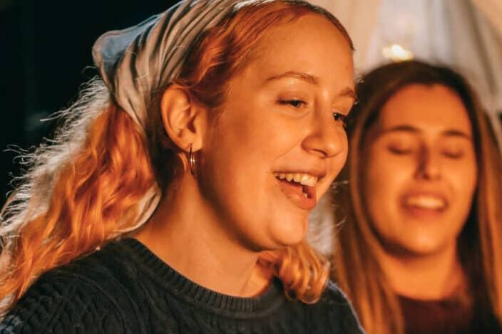 mujeres cantando en una fogata