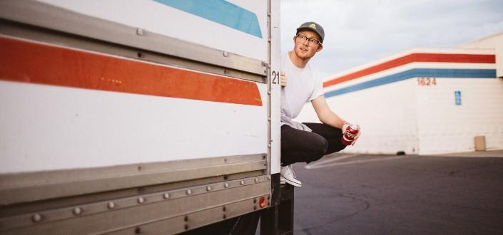 Hombre sentado al borde de un camión con refresco en la mano