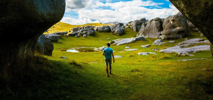 hombre caminando sobre un paisaje verdoso