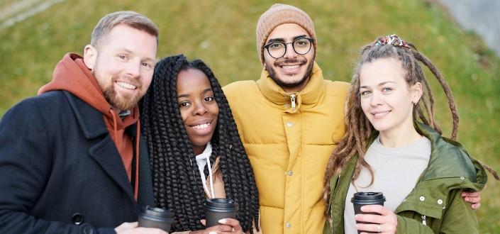 una foto de grupo de amigos sosteniendo una taza de café en un día frío