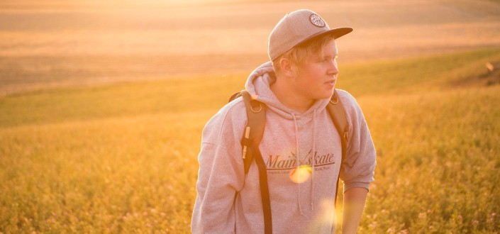 hombre waring una gorra caminando por un campo