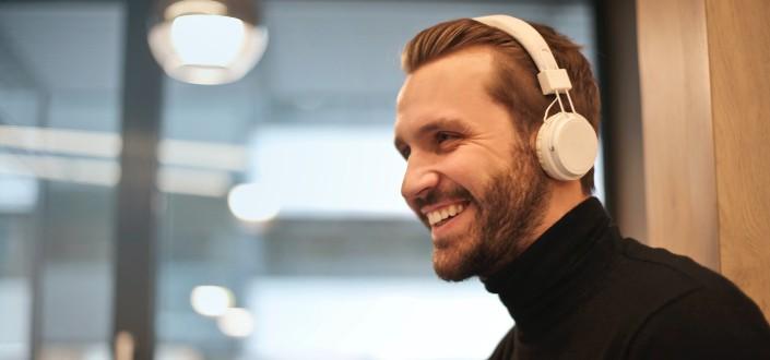 Un hombre sonriente con auriculares en una camisa negra con cuello de tortuga.