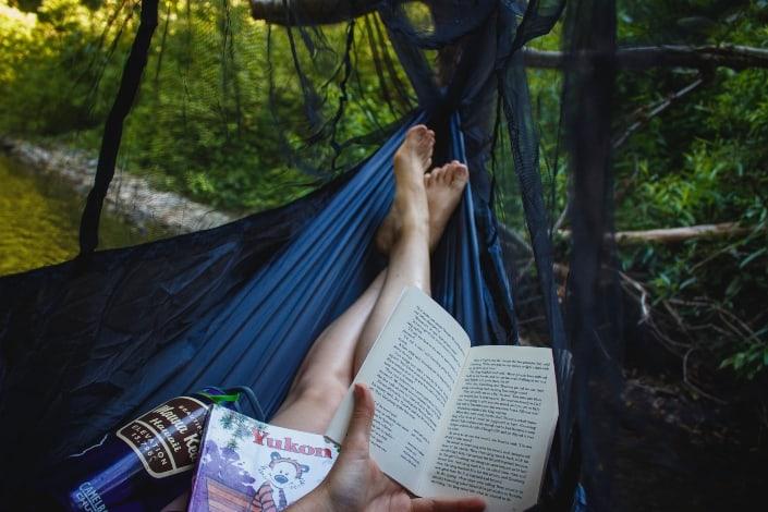Persona sosteniendo un libro y relajándose en la naturaleza.