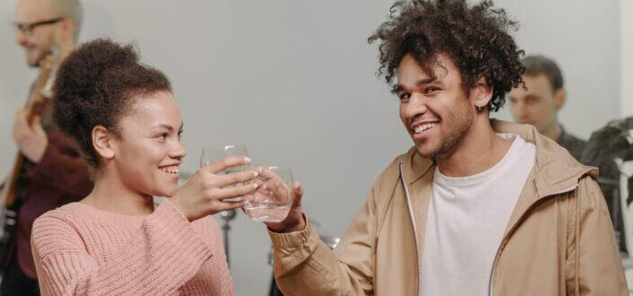 hombre y mujer tintineando sus bebidas