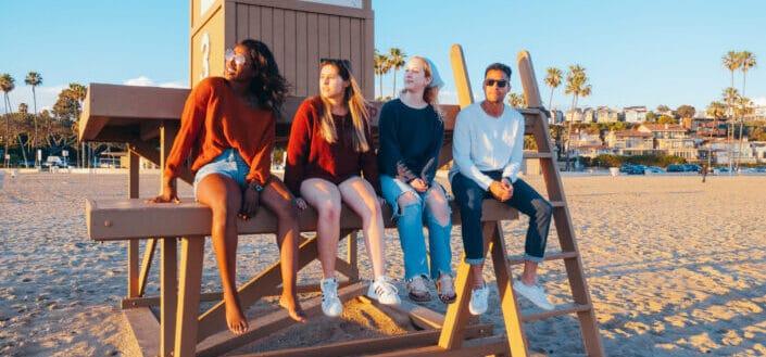 Grupo de amigos viendo la puesta de sol en la playa