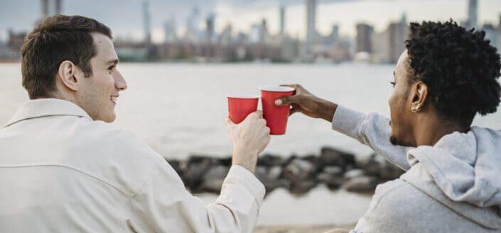 Amigos multiétnicos positivos bebiendo en terraplén