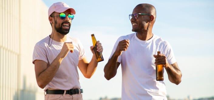 Hombres multiétnicos bebiendo cerveza y bailando en la azotea