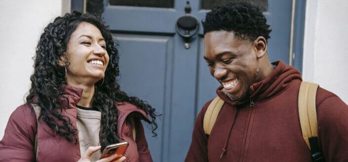 Amigos con teléfonos inteligentes riendo cerca de los edificios