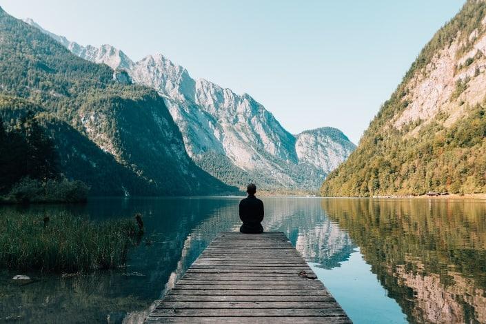 hombre sentado junto al lago disfrutando de su vista