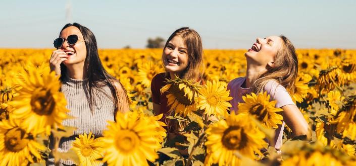 Amigas divirtiéndose en un jardín de girasoles en un día soleado