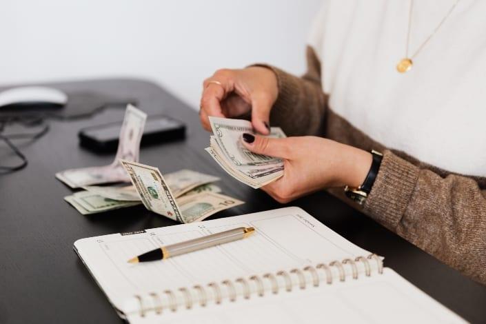 mujer contando su dinero haciendo presupuesto