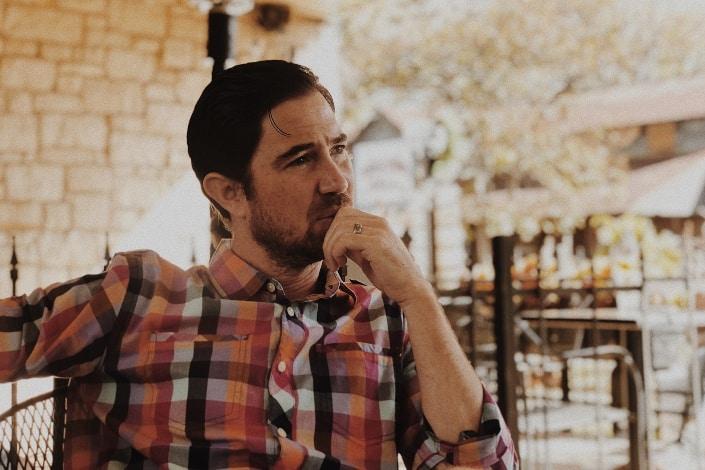 Hombre en camisa de vestir a cuadros teniendo pensamientos profundos