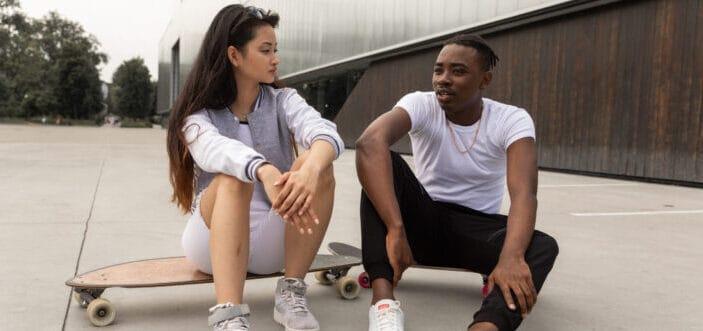 hombre y mujer sentados en sus patinetas compartiendo pensamientos
