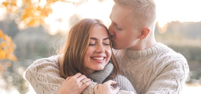 hombre besando a su chica en la cabeza mientras se abraza