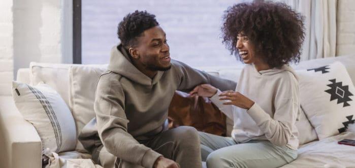pareja sentada en un sofá teniendo una conversación divertida