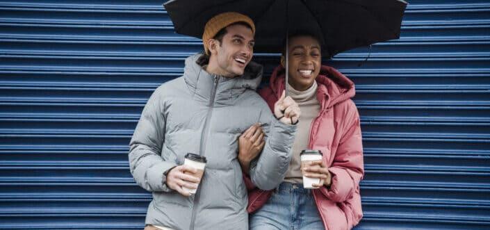 hombre y mujer alegres con café en sus manos compartiendo un paraguas